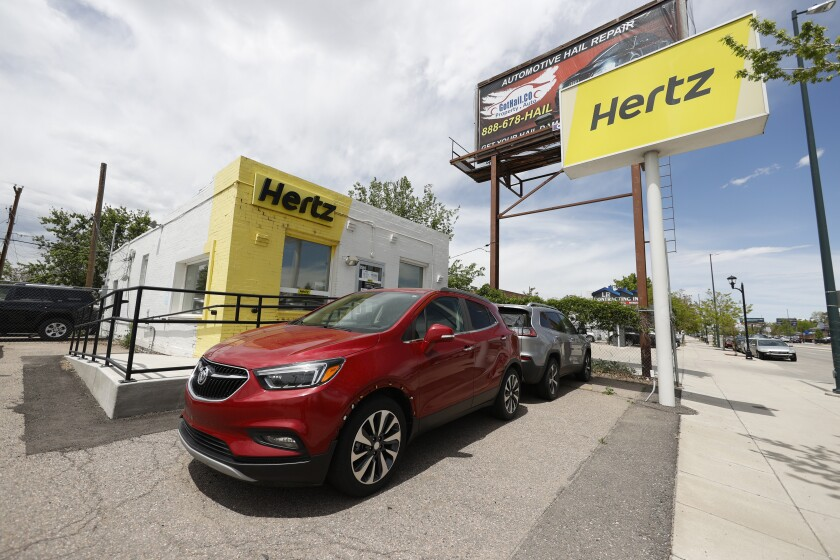 This May 23, 2020, photo shows rental vehicles parked outside a closed Hertz car rental office in south Denver. Hertz said Wednesday, June 17, it has put its plans to sell $500 million worth of stock on hold because the offering is being reviewed by the Securities and Exchange Commission. (AP Photo/David Zalubowski)