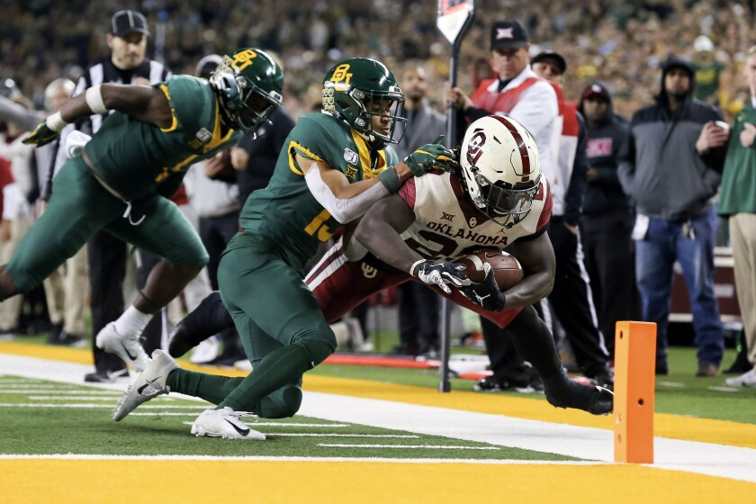 Oklahoma running back Rhamondre Stevenson is pushed out of bounds by Baylor cornerback Raleigh Texada.
