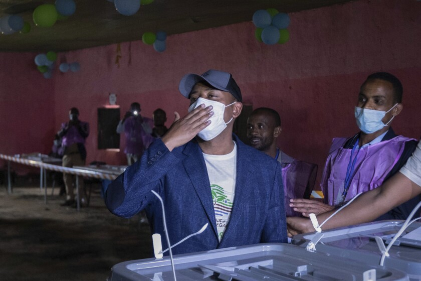 Abiy Ahmed holds his hand over his face mask at a polling place