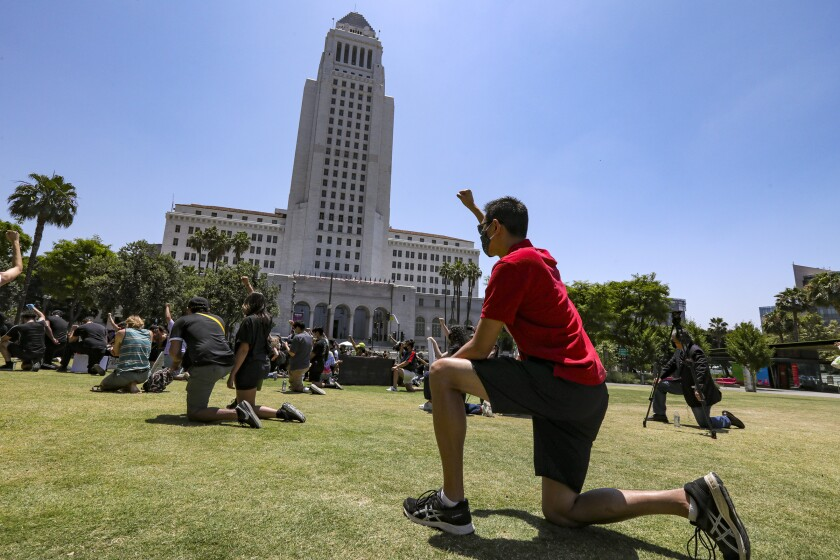 A man takes a knee in front of Los Angeles City Hall with other people protesting police brutality.
