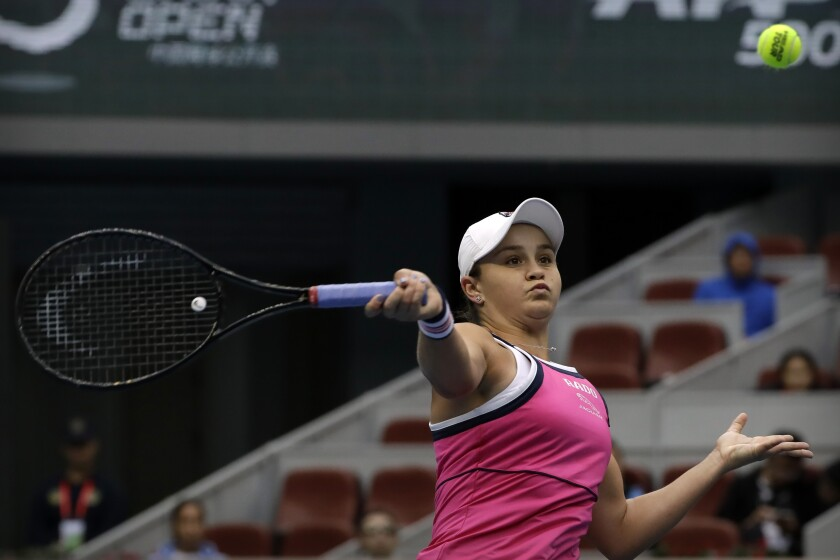 Ashleigh Barty of Australia hits a return shot while competing against Kiki Bertens of the Netherlands in their semifinal match in the China Open tennis tournament in Beijing, Saturday, Oct. 5, 2019. (AP Photo/Mark Schiefelbein)