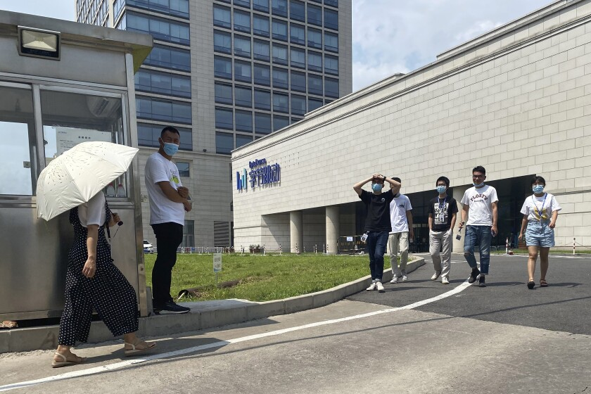 Employees exit the ByteDance headquarters in Beijing, China on Friday, Aug. 7, 2020. President Donald Trump on Thursday ordered a sweeping but unspecified ban on dealings with the Chinese owners of consumer apps TikTok and WeChat, although it remains unclear if he has the legal authority to actually ban the apps from the U.S. TikTok is owned by Chinese company ByteDance. (AP Photo/Ng Han Guan)