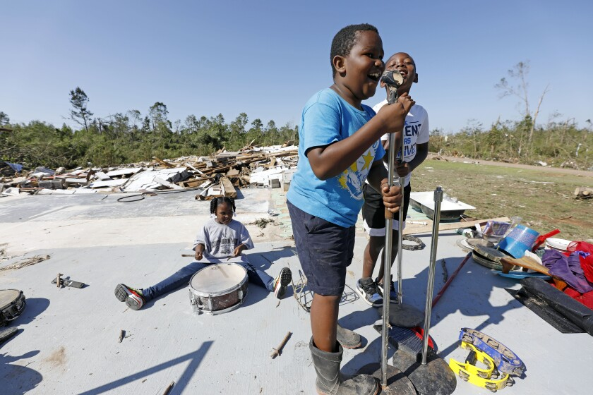 Children play in a neighborhood in Prentiss, Miss., damaged by a tornado April 12.