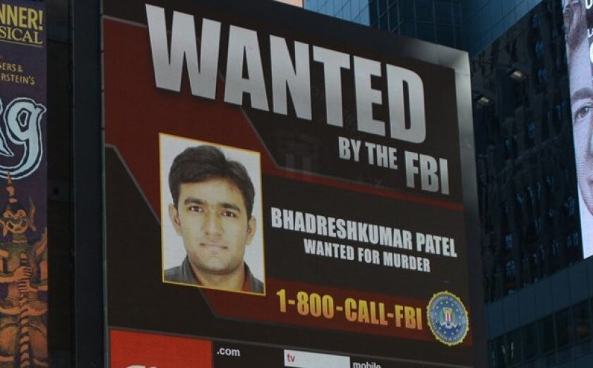 This Nov. 4, 2015 photo provided by the FBI shows a Times Square video screen image of Bhadreshkumar Patel in New York.  The FBI announced Friday, Nov. 6, 2015 that the U.S. Attorney's office has issued a federal warrant for Bhadreshkumar Patel for unlawful flight to avoid prosecution. He's charged