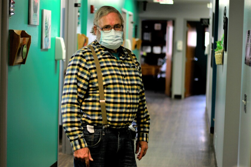 Dr. Tom Dean, in jeans, flannel, suspenders and mask, stands inside his clinic in Wessington Springs, S.D.