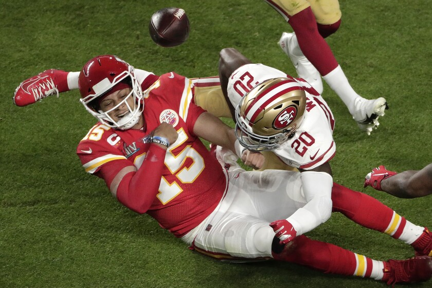 The 49ers' Jimmie Ward jars the ball loose from the hands of Patrick Mahomes, who had run for a first down until he fumbled the ball backward.