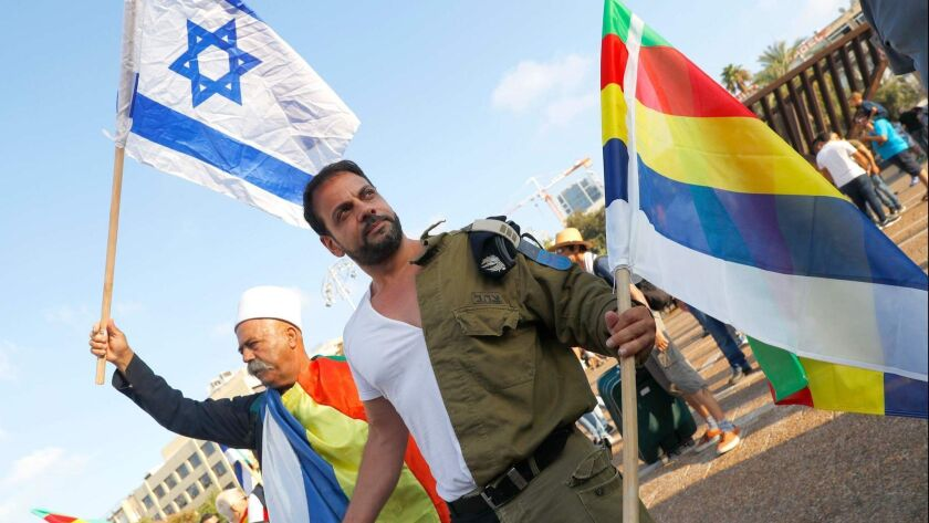 A Druze and Israeli veteran carry Israel and Druze flags. The Israeli veteran also wears an outfit that combines civilian clothes with a military uniform.