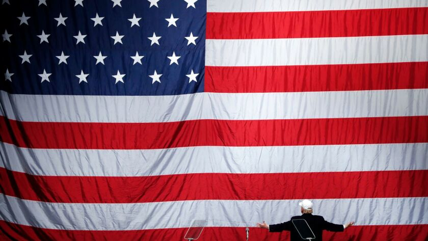 Then-Republican presidential candidate Donald Trump turns to the American flag at a campaign rally in Sterling Heights, Mich. on Nov. 6, 2016.