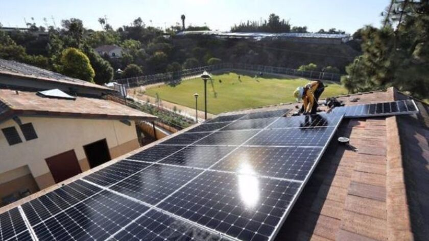Electrician Matt Fausher of Sullivan Solar Power installs solar panels on the roof of a classroom building at Saint John the Evangelist School in Encinitas on Dec. 1, 2016.