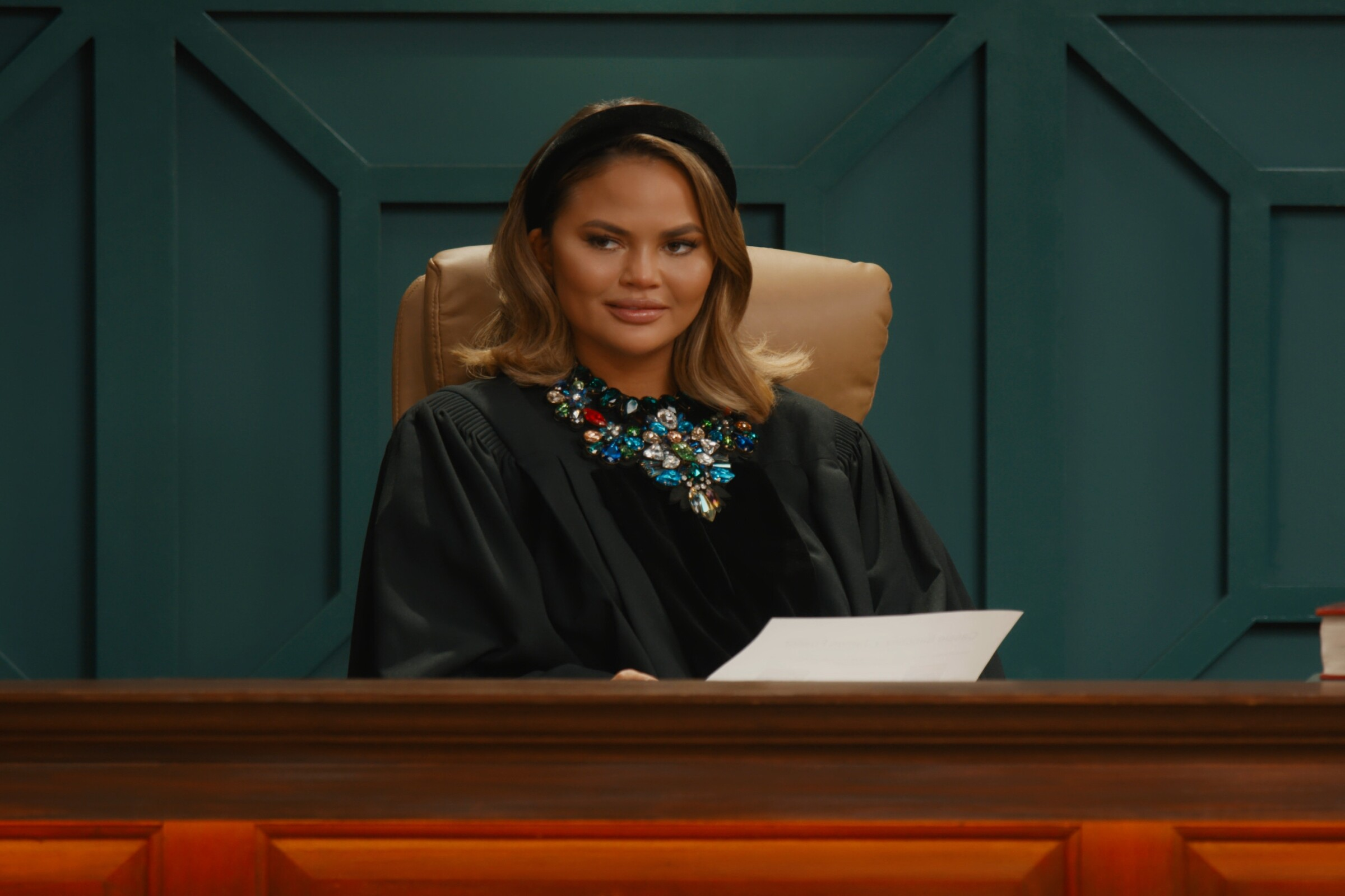 Chrissy Teigen wearing judge's robes at a court-style bench.