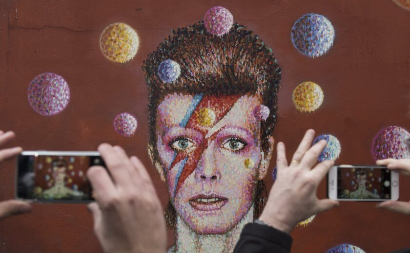 People take photographs of a mural of David Bowie in the London district of Brixton, where the British singer was born. Bowie died Sunday at age 69.
