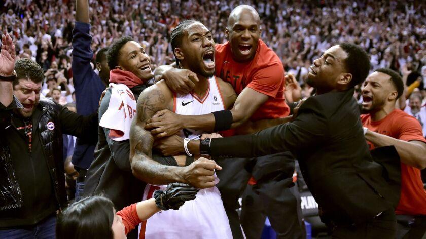 Toronto Raptors forward Kawhi Leonard, center, celebrates his game-winning basket as time expired at
