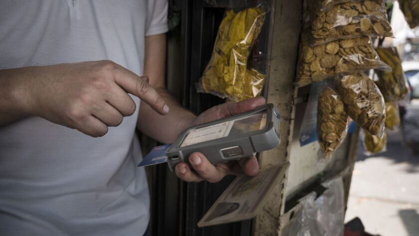 A street vendor uses a portable cash reader to sell a chocolate bar at a kiosk in Caracas.