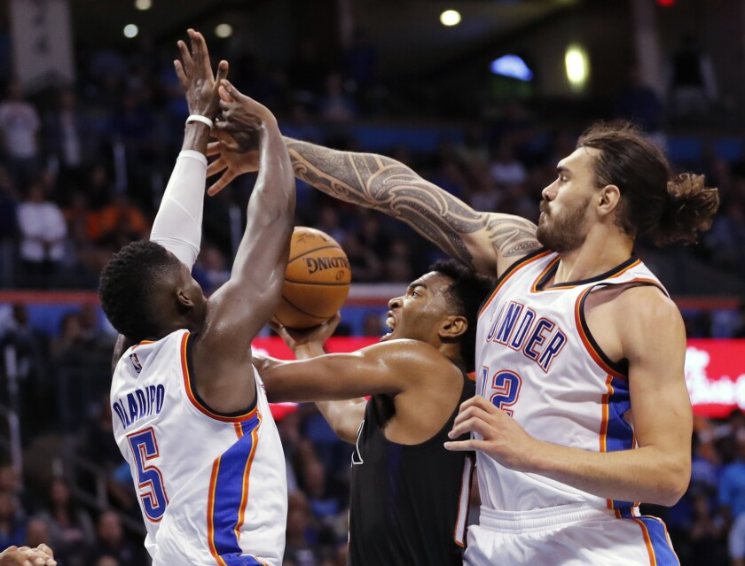 Suns forward T.J. Warren (12) is caught between Oklahoma City Thunder guard Victor Oladipo (5) and center Steven Adams (12) during the second half of a game on Oct. 28.