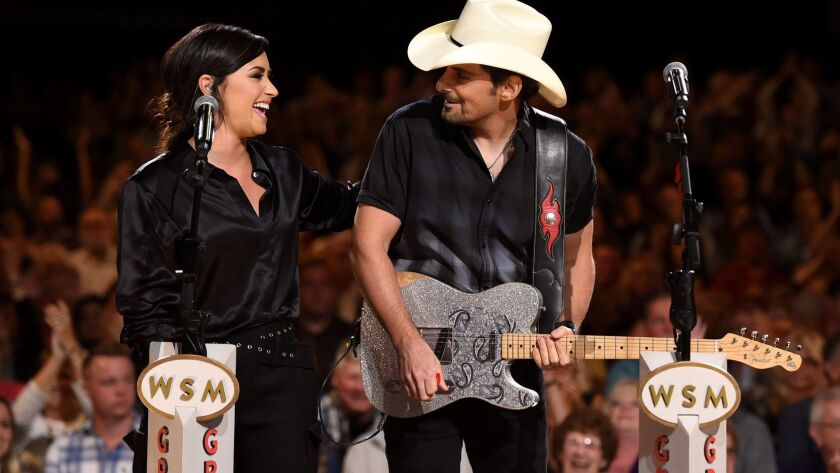 Demi Lovato and Brad Paisley perform at a 2017 hurricane relief concert at the Grand Ole Opry House in Nashville, Tenn.