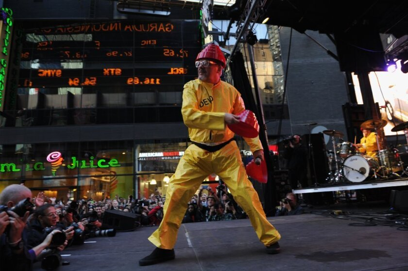 "Devo's Mark Mothersbaugh tosses ""energy dome"" headwear to a crowd in New York's Times Square. The band launched an online store featuring merchandise for coronavirus protection."