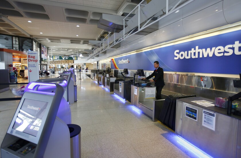 Southwest Airlines customer service agent Guillermo Rosales waits for customers at San Diego International Airport on March 24, 2020.