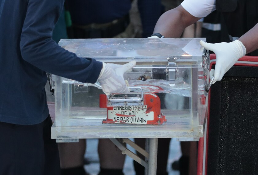 Members of the National Transportation Safety Committee carry a box containing the flight data recorder
