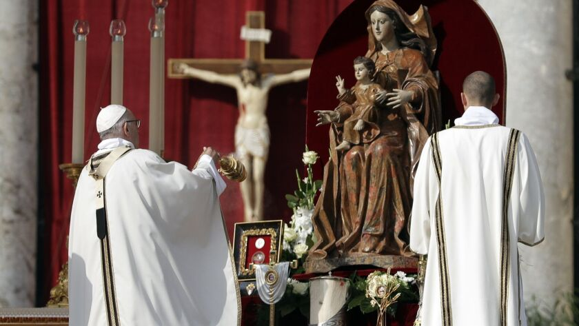 Pope Francis incenses the relics during a canonization ceremony in St. Peter's Square at the Vatican