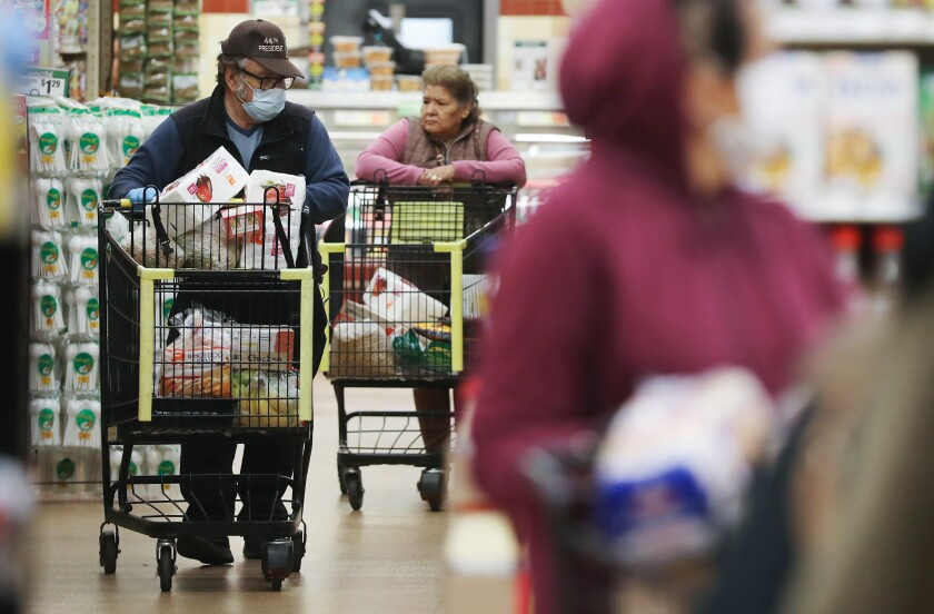 Seniors shop for groceries during special hours open to seniors and the disabled at Northgate Gonzalez Market.