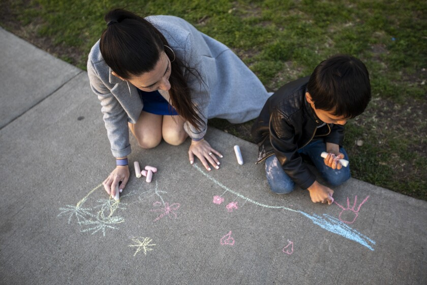 A mother and son draw with chalk on the sidewalk