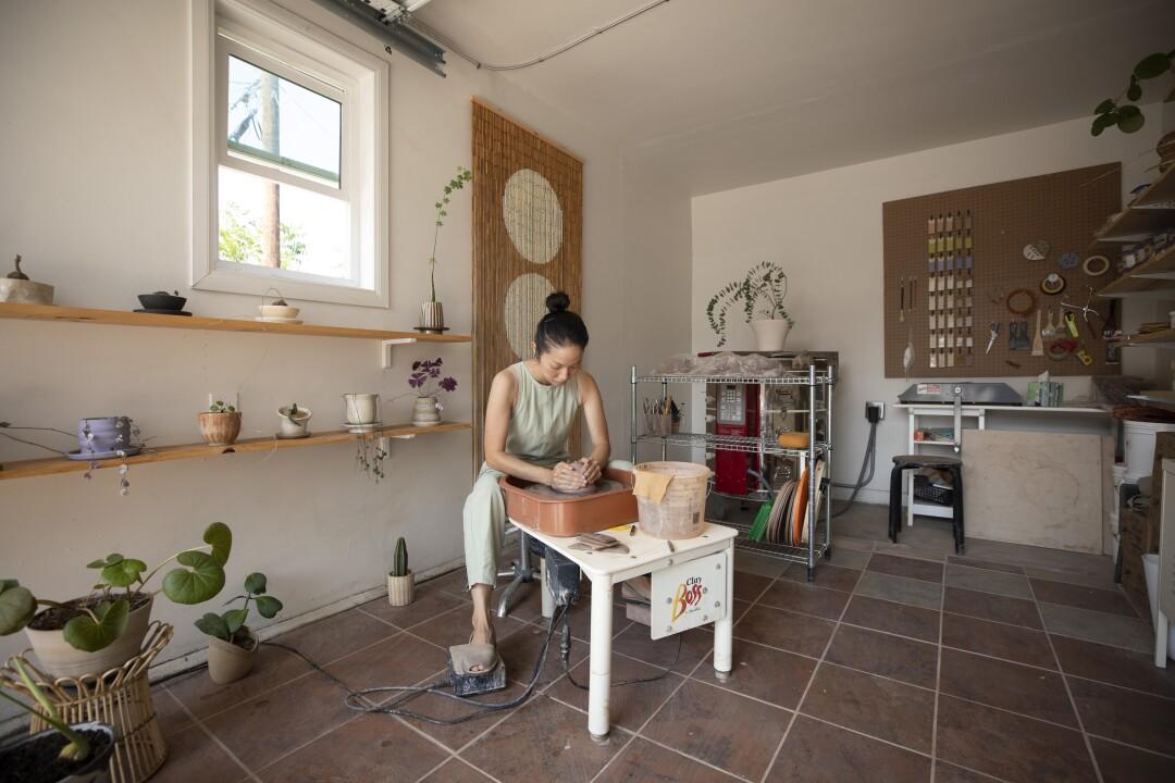 studio woman shaping clay on ceramic wheels