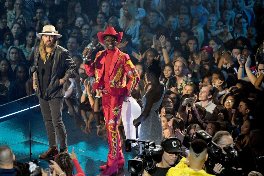 Lil Nas X in a custom Union Western Clothing suit, Gladys Tamez Millinery hat and pskaufman boots, accepting one of his MTV Video Music Awards with Billy Ray Cyrus in August 2019.