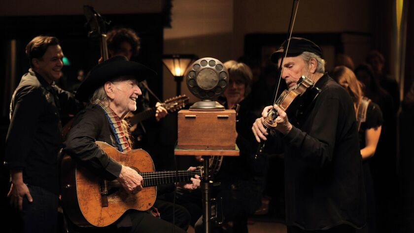 """Willie Nelson, left, and the late Merle Haggard recording """"Old Fashioned Love"""" for """"The American Epi"""