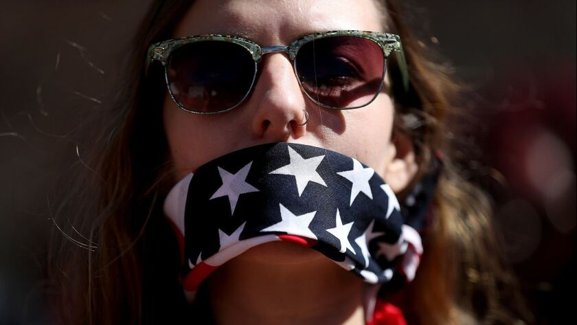 A protester wears a bandana over her mouth to support women's health programs and protest the White House global gag rule on March 8, 2017 in Washington.