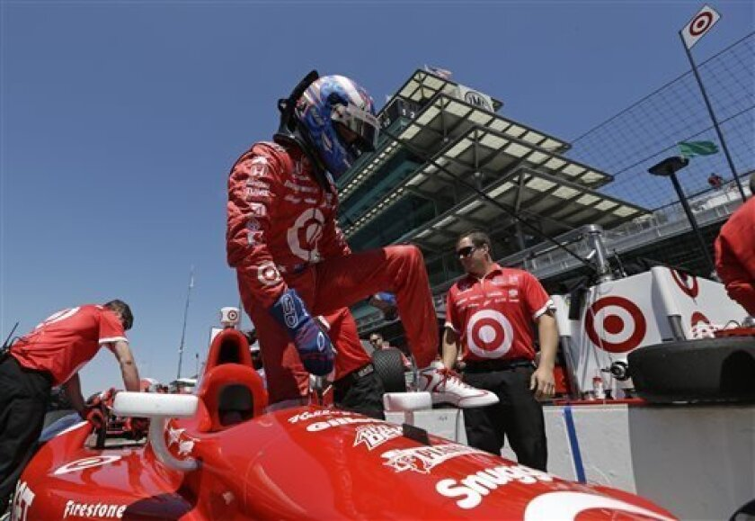 Scott Dixon, of New Zealand, climbs out of his car during practice for the Indianapolis 500 auto race at the Indianapolis Motor Speedway in Indianapolis, Monday, May 13, 2013. (AP Photo/Darron Cummings)