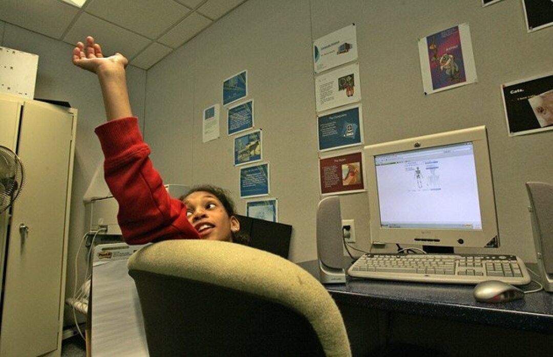 Bre-Anna Perez, 10, raised her hand in a biology class at the Elementary Institute of Sciences after she completed putting together a skeleton on the computer. (Peggy Peattie / Union-Tribune)