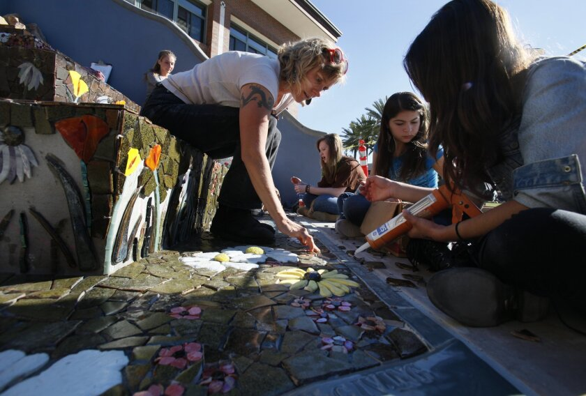Coronado High School artist-in-residence Kirstin Green works with students creating a large mosaic at the school.