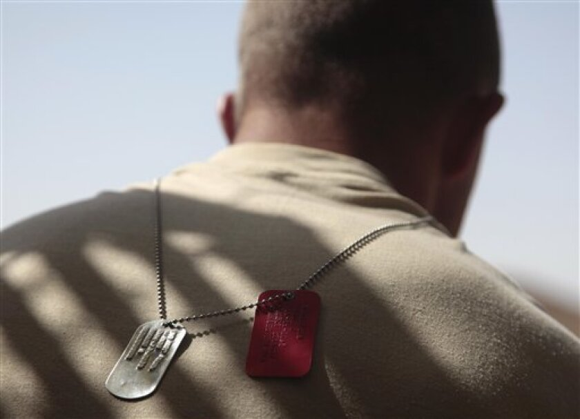 In this May 21, 2010 photo, the dog tags of United States Army Staff Sgt. Rande Henderson of Helena, Mont. hang over his back as he rises early in the morning in the Shah Wali Kot district of Afghanistan's Kandahar province. Henderson is the platoon sergeant for 2nd Platoon of Charlie Company, 1st Battalion, 17th Infantry Regiment of the 5th Stryker Brigade, 2nd Infantry Division. Twenty-two men in the U.S. Army's 1st Battalion, 17th Infantry Regiment of 800 died in a yearlong Afghan tour ending this summer. Most were killed last year in the Arghandab, a gateway to the southern city of Kandahar. About 70 were injured, all but two in bomb blasts. (AP Photo/Julie Jacobson)