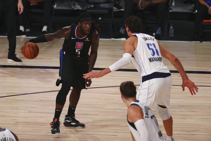 Clippers forward Montrezl Harrell looks to drive against Mavericks center Boban Marjanovic during Game 1 on Aug. 17, 2020.