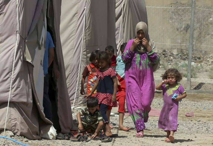 A displaced woman and children walk through rows of tents at a camp set up for people from Ramadi and the area in al-Shurta neighborhood of west Baghdad, Iraq, Thursday, April 30, 2015. There are 2.7 million people internally displaced in Iraq, where government forces are struggling to wrest back v