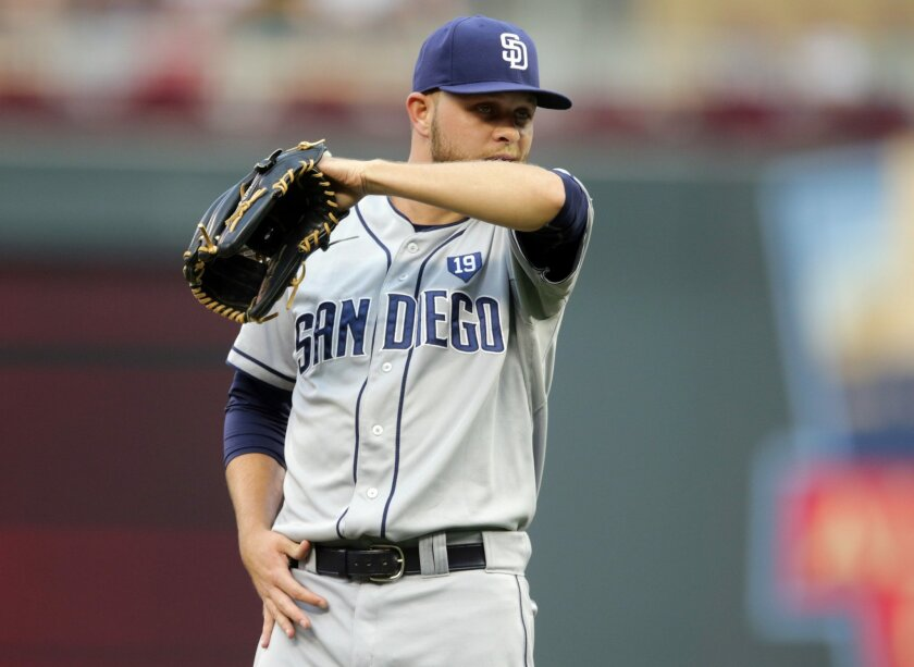 San Diego Padres pitcher Jesse Hahn wipes his chin as he gave up a walk to Minnesota Twins' Trevor Plouffe in the first inning of a baseball game, Tuesday, Aug. 5, 2014, in Minneapolis. (AP Photo/Jim Mone)