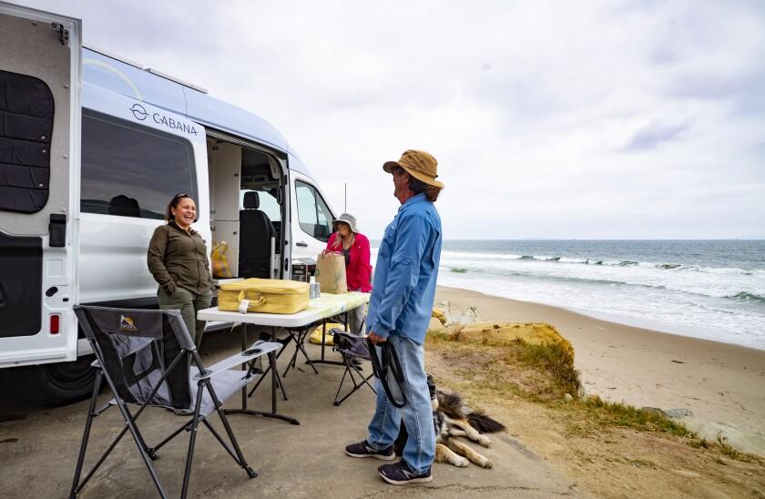 A ranger talks with a man next to a van on the beach
