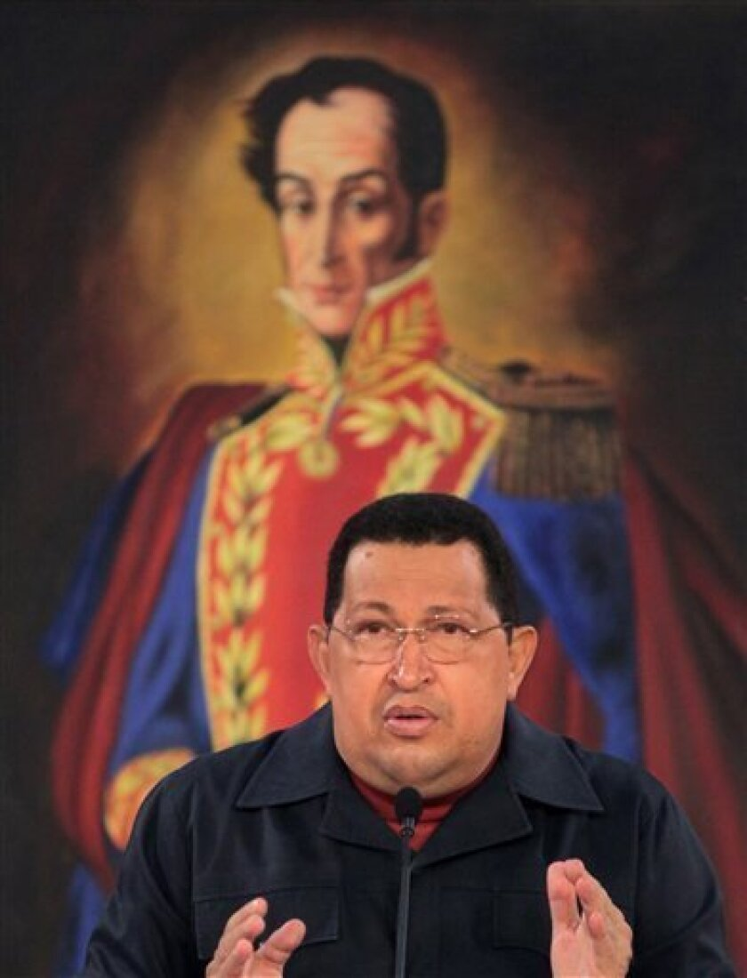 In this photo released by Miraflores Press Office, Venezuela's President Hugo Chavez, speaks during a televised speech, backdropped by a framed image of Venezuela's independence hero Simon Bolivar, at Miraflores presidential palace in Caracas, Venezuela, Saturday March 31, 2012.  Chavez said Saturd