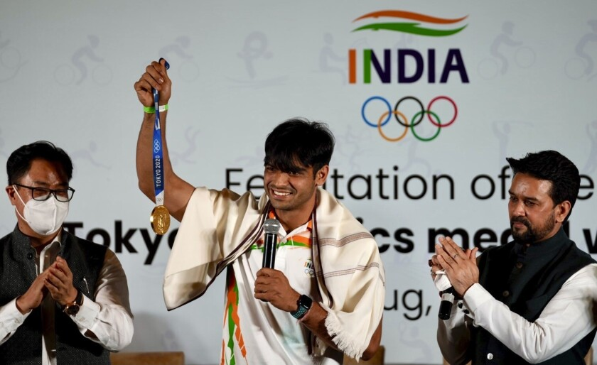 Indian ministers Kiren Rijiju, left and Anurag Thakur, right, applaud as Olympic medallist Neeraj Chopra displays the gold medal he won in the men's javelin at the Tokyo Games during a felicitation function at Major Dhyan Chand National Stadium in New Delhi, India, Monday, Aug.9 2021. (AP Photo/Manish Swarup)