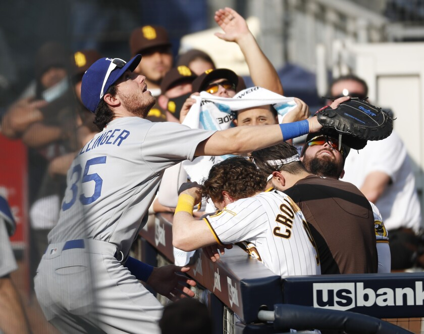 Cody Bellinger of the Los Angeles Dodgers tries to catch a foul ball in front of Padres dugout Wednesday.