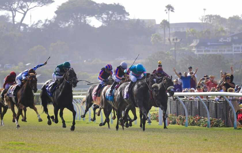 Horses make the final turn on opening day for Del Mar last July.