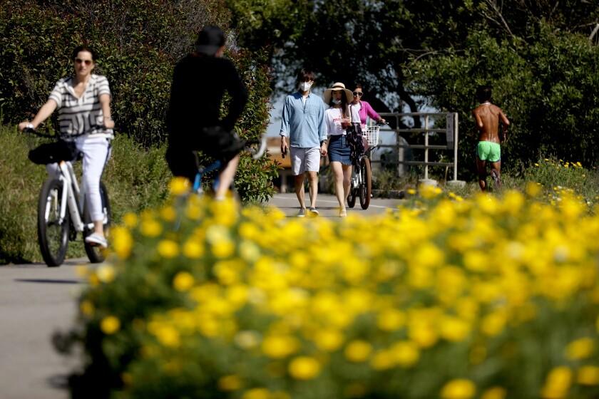Peple walk along a trail at the beach in Ventura.