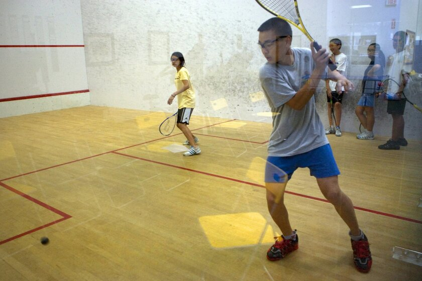 William Quan (right) prepared a stroke against Ana Rodriguez during practice with Surf City Squash. Thirty youths are involved in the program. (Nelvin C. Cepeda / Union-Tribune)