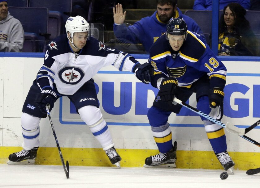 Winnipeg Jets' Alexander Burmistrov, of Russia, and St. Louis Blues' Jay Bouwmeester, right, reach for a loose puck during the first period of an NHL hockey game Tuesday, Feb. 9, 2016, in St. Louis. (AP Photo/Jeff Roberson)