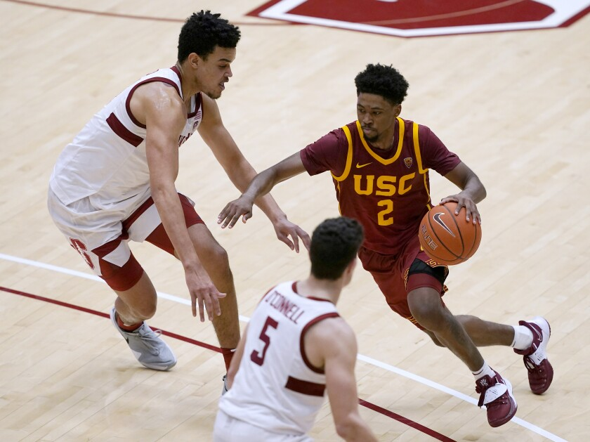 Southern California guard Tahj Eaddy (2) moves the ball between Stanford forward Spencer Jones, left, and guard Michael O'Connell (5) during the second half of an NCAA college basketball game in Stanford, Calif., Tuesday, Feb. 2, 2021. Southern California won 72-66.(AP Photo/Tony Avelar)
