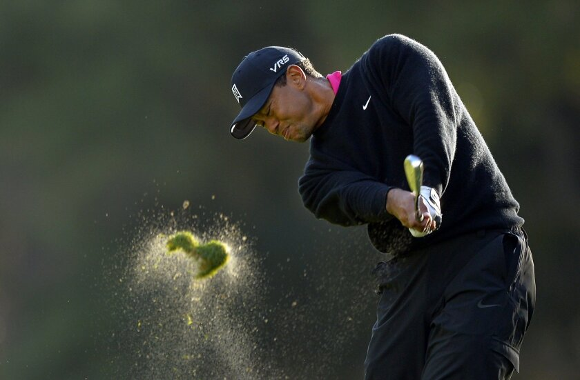 Tiger Woods hits his approach shot on the 18th hole during the second round of the Northwestern Mutual World Challenge golf tournament at Sherwood Country Club, Friday, Dec. 6, 2013, in Thousand Oaks, Calif. (AP Photo/Mark J. Terrill)