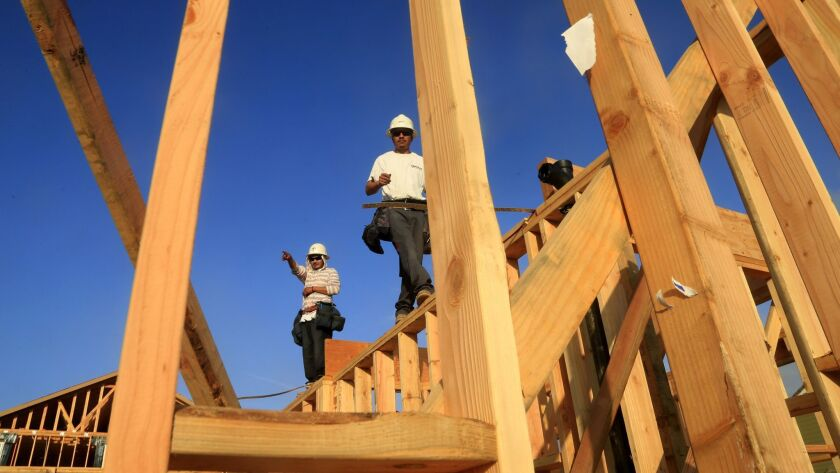 Framers walk along the top of the newly constructed walls of a home in Irvine neighborhood in 2014.