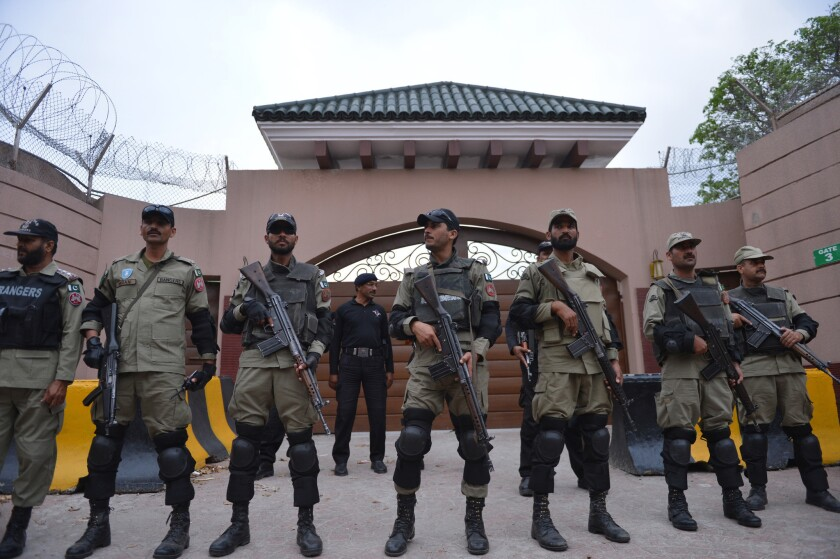 Pakistani paramilitary soldiers stand guard last week outside the residence where former President Pervez Musharraf is being held under house arrest. A court on Tuesday banned Musharraf from Pakistani politics for life.