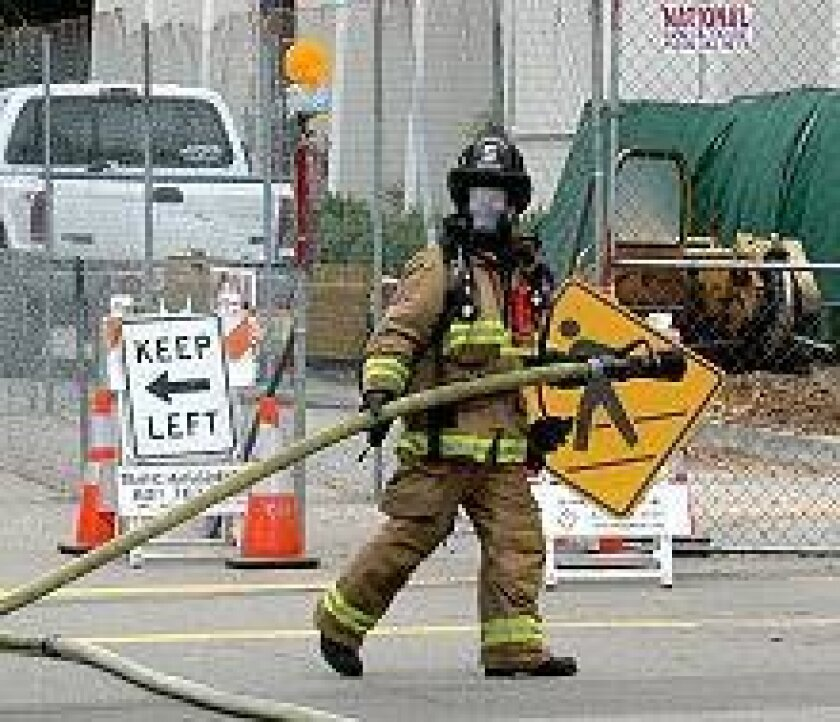 A firefighter positions a hose line near St. Vincent Church after a private contractor accidentally ripped open a 4-inch gas line while grinding up a tree stump next to the church.