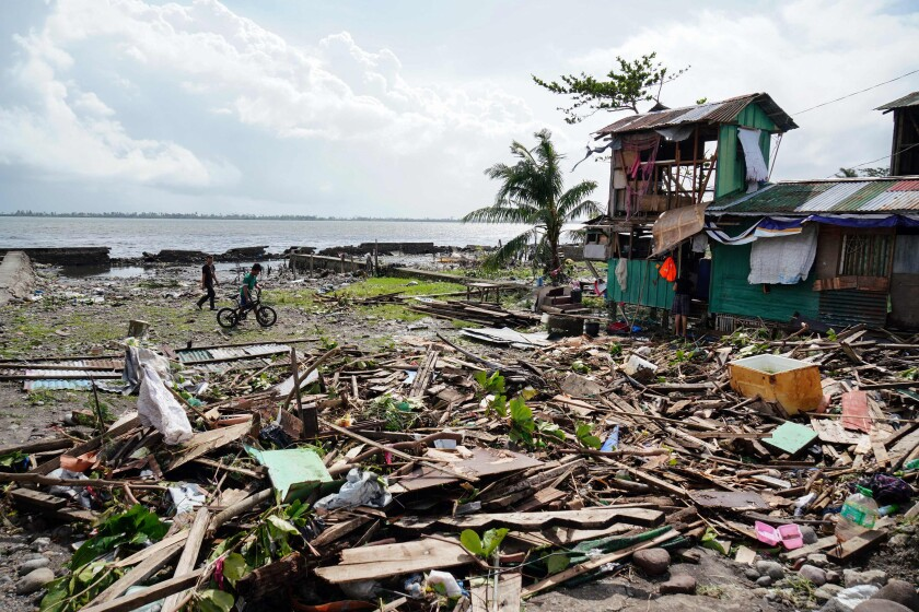 Residents walk past a house damaged during Typhoon Phanfone in Tacloban, Leyte province in the central Philippines.